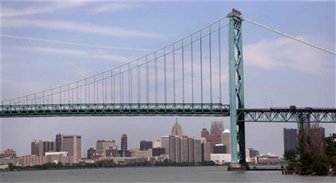 The Detroit city skyline is seen behind the Ambassador Bridge, an international border-crossing linking Windsor, Ontario with Detroit, along
