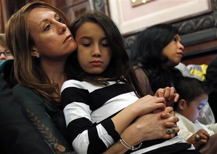 Theresa Volpe (L) holds her daughter Ava (2nd L) as her partner Mercedes Santos sits with their son Jaidon after testifying at the Illinois