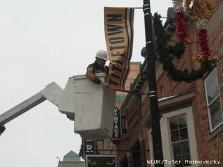 Green Bay Mayor Jim Schmitt hangs a Titletown banner on a downtown street light post Jan. 3, 2013, two days before the Green Bay Packers host the Minnesota Vikings in a Wild Card NFL playoff game. (courtesy of FOX 11).