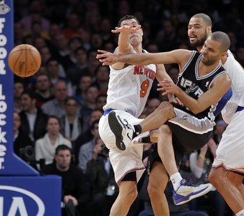 San Antonio Spurs guard Tony Parker (C) slams into New York Knicks guard Pablo Prigioni (L) as he passes in the first quarter of their NBA b