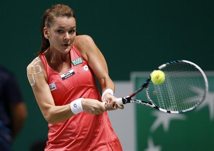 Poland's Agnieszka Radwanska hits a return to Serena Williams of the U.S. during their semifinals WTA tennis championships match in Istanbul