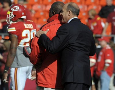 Kansas City Chiefs head coach Romeo Crennel (L) is hugged by general manager Scott Pioli before the start of their NFL game against the Caro