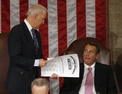 U.S. Vice President Joe Biden (L) holds the presidential election electoral college vote certificate representing the state of Ohio alongsid