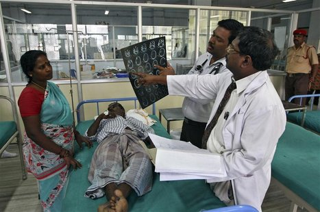 Doctors examine a magnetic resonance imaging (MRI) scan of a patient lying on a bed inside a ward at Rajiv Gandhi Government General Hospita