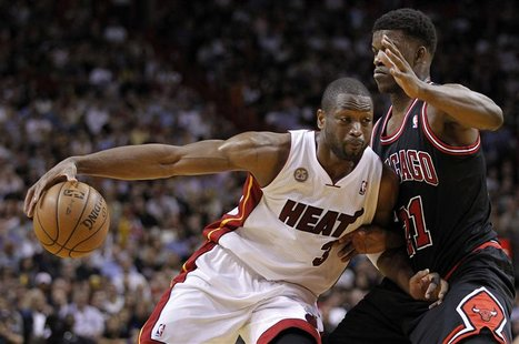 Miami Heat's Dwyane Wade (L) drives against Chicago Bulls' Jimmy Butler in the first half of their NBA basketball game in Miami, Florida Jan