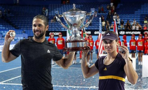 Fernando Verdasco (L) and Anabel Medina Garrigues of Spain hold up the Hopman Cup and their diamond encrusted silver tennis balls after defe