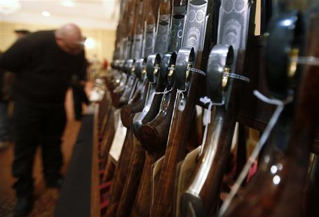 A man looks at a shotgun during the East Coast Fine Arms Show in Stamford, Connecticut, January 5, 2013. The show is being held despite the