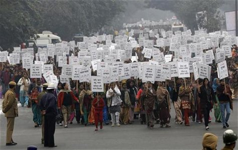 Women hold placards as they march during a rally organized by Delhi Chief Minister Sheila Dikshit (unseen) protesting for justice and securi