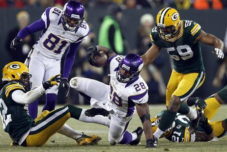 Minnesota Vikings running back Adrian Peterson (28) is brought down by Green Bay Packers inside linebacker Brad Jones (59) during their NFL