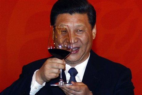 Chinese Vice-President Xi Jinping holds a glass of red wine as he toasts at a dinner, also attended by former U.S. secretary of state Henry