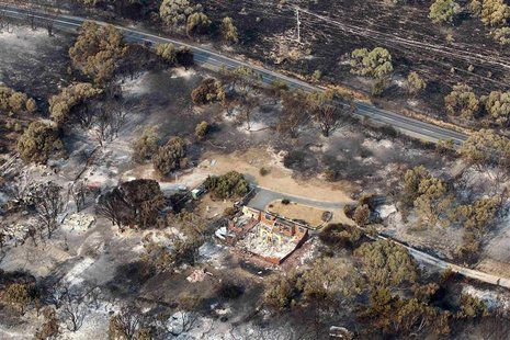 The debris of houses destroyed by a bushfire is seen in Dunalley, about 40 kilometres (25 miles) east of Hobart, January 5, 2013. REUTERS/Ch