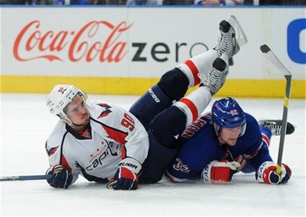 Washington Capitals' Marcus Johansson (L) is knocked to the ice by a sliding New York Rangers' Anton Stralman in the second period during Ga