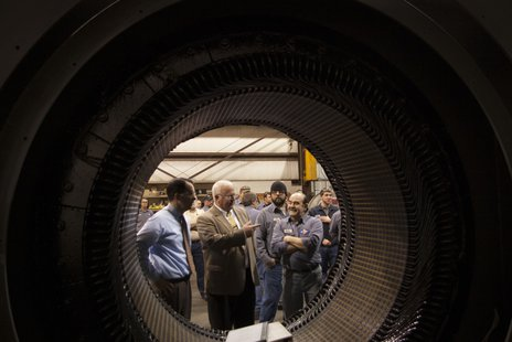 L&S Electric Vice President Paul Gulllickson with Governor Scott Walker as they look at a 6,000 horsepower electric motor that is being reconditioned for a Hibbing Minnesota mine.  The picture is taken through the unfinished motor.