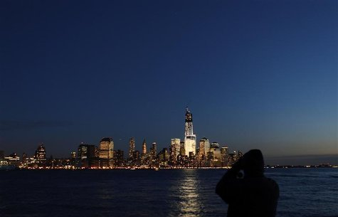 A man photographs the skyline of Lower Manhattan in New York from a park along the Hudson River in Hoboken, New Jersey, December 28, 2012. R