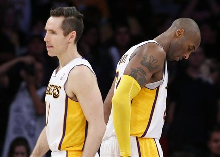 Los Angeles Lakers' Steve Nash (L) and Kobe Bryant walk on the court during the final minute of their loss to the Denver Nuggets during an N