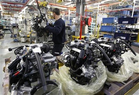 An employee at the Smart Cars factory is seen surrounded by engines as he works on the Smart Fortwo assembly line in Hambach, eastern France