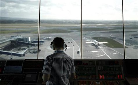 An air traffic controller monitors aircraft movement from the control tower at Manchester Airport, northern England, February 3, 2011. REUTE