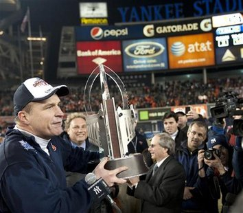 Syracuse University head coach Doug Marrone holds the championship trophy after they beat Kansas State University in their NCAA football Pin