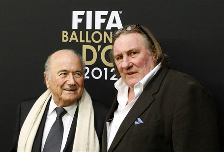 FIFA President Sepp Blatter is accompanied by French actor Gerard Depardieu (R) as he arrives before the FIFA Ballon d'Or 2012 Gala at the K