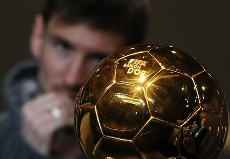 FIFA Men's Ballon d'Or of the Year 2012 nominee Lionel Messi of Argentina watches the trophy during a news conference before the FIFA Ballon