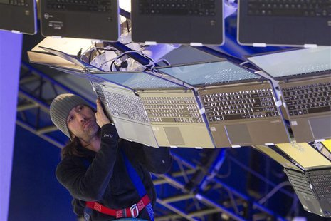 Rigger Matt Gerbracht arranges a display of Ultrabooks powered with Intel processors as workers prepare for the International CES show at th