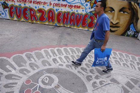 A man walks past a graffiti depicting Venezuelan President Hugo Chavez in Caracas January 7, 2013. The wall reads: 'Force Chavez'. REUTERS/J