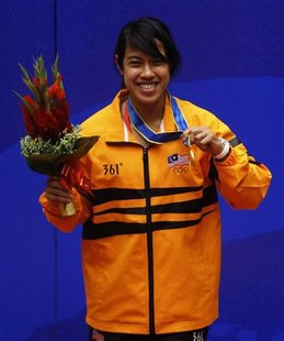 Nicol Ann David of Malaysia holds her gold medal after winning the women's single squash final at the 16th Asian Games in Guangzhou, Guangdo