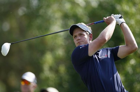 Luke Donald of England watches his shot from the third tee during the final round of the DP World Tour Championship at Jumeirah Golf Estates