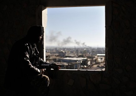 A Free Syria Army fighter watches from his position during a fight with forces loyal to President Bashar al Assad at the front line in Alepp