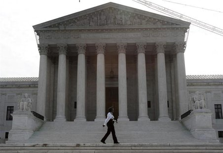 A police officer patrols the front of the U.S. Supreme Court prior to the swearing in of judge Sonia Sotomayor to the Court in Washington, A