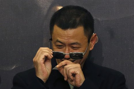 "Hong Kong director Wong Kar-Wai removes confetti from his sunglasses after he beats a drum with cast members at the premiere of the movie ""T"