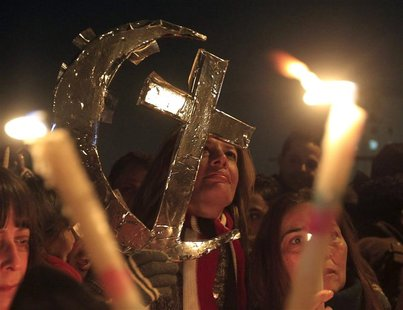 Egyptian Muslims and Christians celebrate Coptic Christmas eve mass at Tahrir Square in Cairo January 6, 2013. With the economic downturn an
