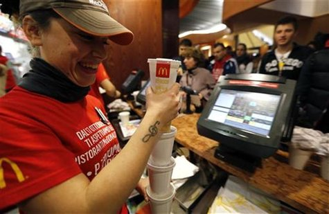 A McDonald's staff member serves soft drinks at their fast food restaurant in downtown Milan October 16, 2012. REUTERS/Stefano Rellandini