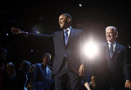 U.S. President Barack Obama (L) points to the crowd during his election night victory rally in Chicago, November 7, 2012, alongside Vice Pre