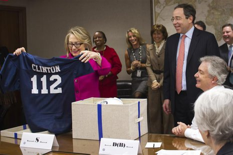U.S. Secretary of State Hillary Clinton holds up a football jersey with her name on it, presented by Deputy Secretary of State Thomas Nides