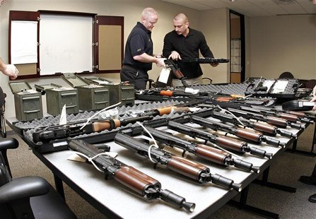Phoenix Bureau of Alcohol, Tobacco, Firearms & Explosives (ATF) special agents Tom Mangan (L) and Peter Forcelli examine a confiscated AK-47