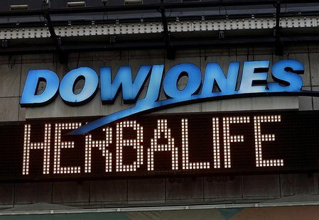"A news headline displaying ""Herbalife"" is seen under the DowJones electronic ticker at Times Square in New York January 9, 2013. REUTERS/Sha"