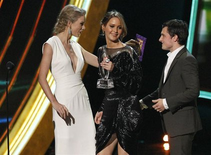 "Taylor Swift presents the award for ""Favorite Movie"" to cast members of the ""Hunger Games"" at the 2013 People's Choice Awards in Los Angeles"