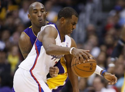 Los Angeles Clippers' Chris Paul (R) dribbles the ball as Los Angeles Lakers' Kobe Bryant (L) defends him during the second half of their NB