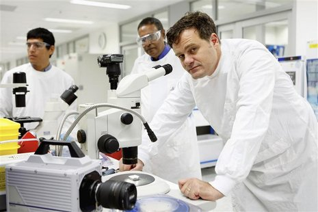 Biomedical engineer Mark Kendall (R) poses beside a stereo microscope in a laboratory in Brisbane in this handout photograph taken in 2012.