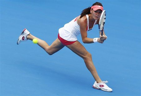 Agnieszka Radwanska of Poland hits a return to Kimiko Date-Krumm of Japan during their women's singles match at the Sydney International ten
