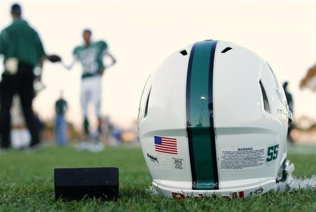 A football helmet's health warning sticker is pictured between a U.S. flag and the number 55, in memory of former student and NFL player Jun