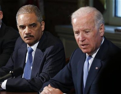 U.S. Attorney General Eric Holder (L) listens to U.S. Vice President Joe Biden speak to representatives of gun safety and gun violence victi