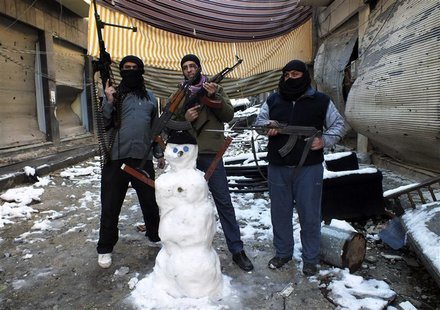 Members of the Free Syrian Army pose with their weapons and a snowman at the Jouret al Shayah area in Homs January 10, 2013. Picture taken J