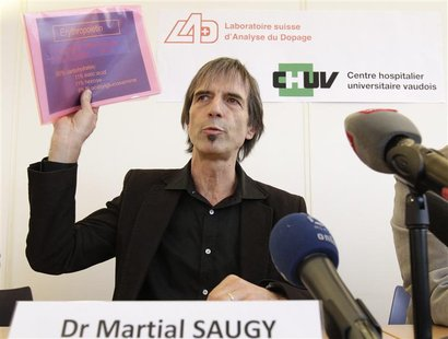 Director of the Swiss anti-doping laboratory Martial Saugy holds papers of a presentation during a news conference in Lausanne January 11, 2