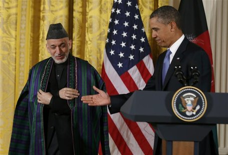 U.S. President Barack Obama (R) welcomes Afghan President Hamid Karzai prior to a joint news conference in the East Room of the White House