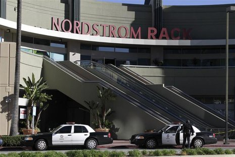 A Los Angeles Police Department officer stands near his vehicle outside the Nordstrom Rack store in the Westchester area of Los Angeles Janu