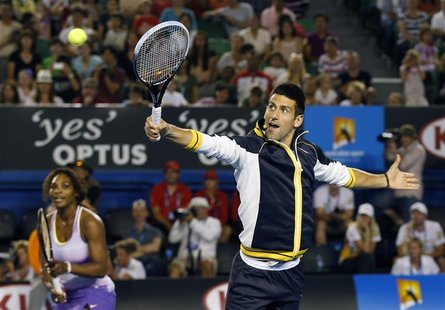 Novak Djokovic of Serbia hits a return as Serena Williams of the U.S. looks on during Kids Tennis Day at the Australian Open tennis tourname