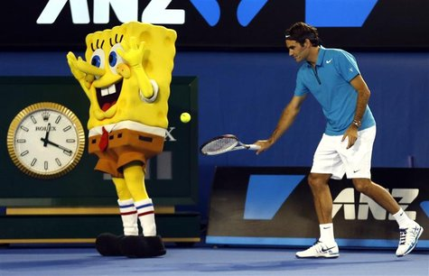 Roger Federer of Switzerland hits a ball into the back of a man dressed as the cartoon character Sponge Bob Square Pants during Kids Tennis