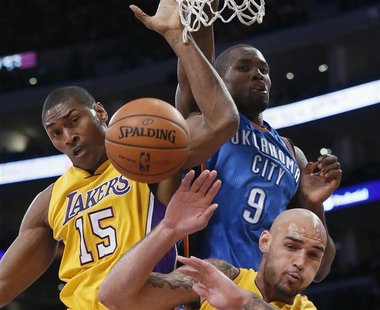 Oklahoma City Thunder's Serge Ibaka (C) fights for a rebound with Los Angeles Lakers Metta World Peace (L) and Robert Sacre of Canada during